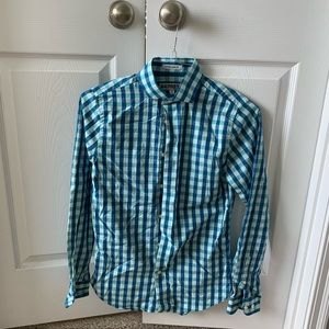 Gingham pattern button up shirt with collar.